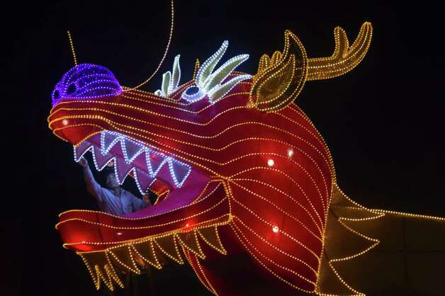 A worker inspects the dragon lantern decoration with energy-saving LED lights at the Fo Guang Shan Dong Zen temple in Jenjarom, some 50 kilometres Southwest of Kuala Lumpur on January 16, 2012.The Chinese Lunar New Year, the year of the dragon, falls this January 23, and will be celebrated by ethnic Chinese worldwide.AFP PHOTO / Mohd Rasfan (Photo credit should read MOHD RASFAN/AFP/Getty Images) Photo: MOHD RASFAN / AFP