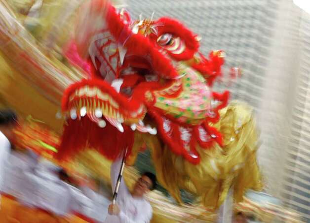 A dragon dance team performs during a street parade in Hong Kong on January 1, 2012 on the New Year's Day holiday. Some 2,000 performers took part in the event including 88 dragons setting a new Guinness world record for the most dragons in a parade.  AFP PHOTO / Dale de la Rey (Photo credit should read DALE de la REY/AFP/Getty Images) Photo: DALE DE LA REY / AFP