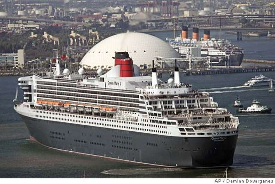 The Queen Mary 2, the world's largest ocean liner, bottom left, moves near its historic namesake the Queen Mary, docked at upper right, Thursday, Feb. 23, 2006, at the Long Beach Harbor, in Long Beach, Calif. The QM2 and the Queen Mary blew their signal horns in a ceremony where the Queen Mary, a 1934 vessel, has been docked as a tourist attraction and hotel for nearly forty years. (AP Photo/Damian Dovarganes) Photo: DAMIAN DOVARGANES