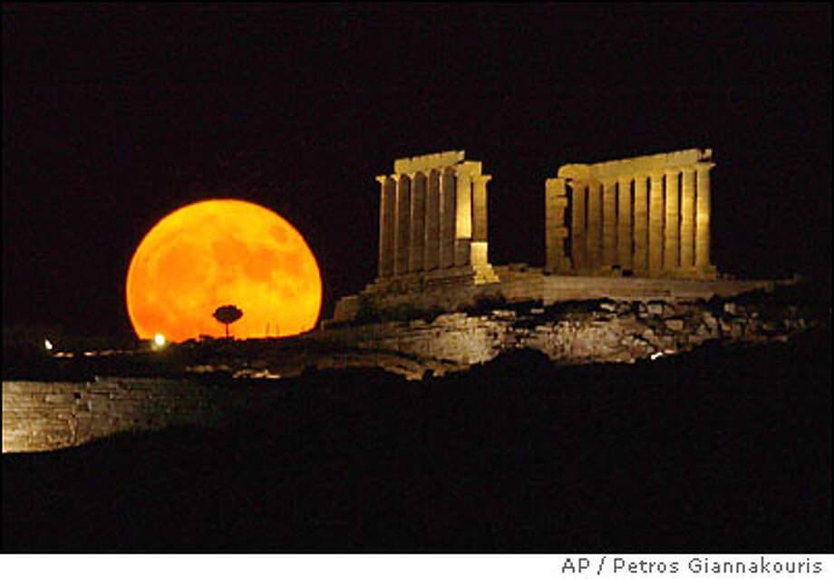"Like a big pizza pie: The ""supermoon"" certainly appears super-sized next to the ancient Greek temple of Poseidon at Cape Sounion, south of Athens. Photo: PETROS GIANNAKOURIS"