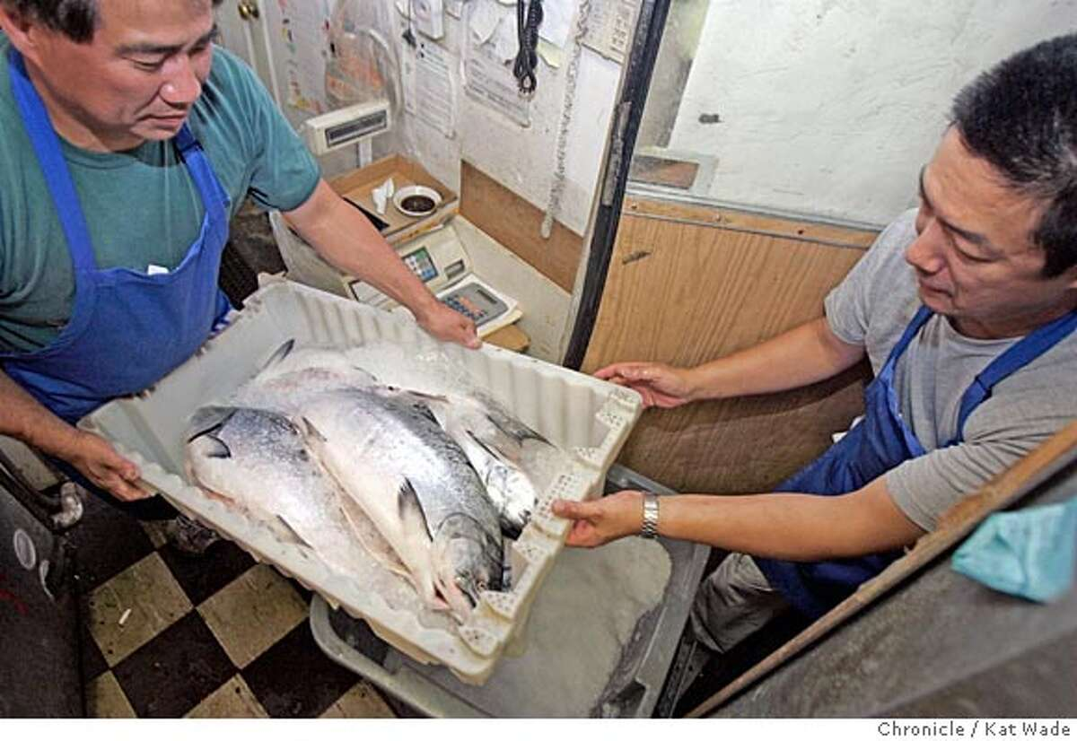 On 7/13/05 in Berkeley at the Tokyo Fish Market, co-owner Lee Nakamura and employee Hiro Watanabe put fresh caught salmon in the freezer at the market which has been in business on San Pablo Ave. in Berkeley for 42 years and is expanding due to their loyal following of both Japanese Americans and non-Asians alike who love the food. Kat Wade/ The Chronicle