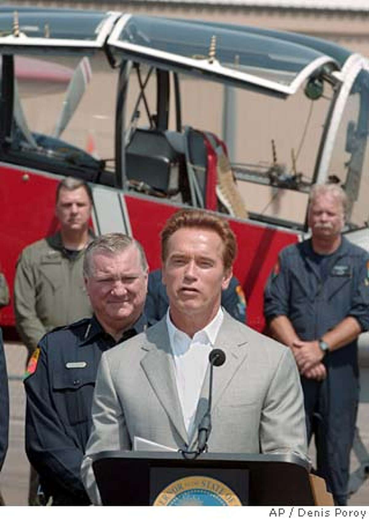 California Gov. Arnold Schwarzenegger speaks at a news conference at Gillespie Field in El Cajon, Calif. held to announce the signing of an executive order to expand statewide firefighting efforts as Dale Geldert, director of Forestry and Fire Protection, left, looks on Wednesday, July 20, 2005. Behind him is a firefighting airplane and its crew. (AP Photo/Denis Poroy) Ran on: 07-21-2005