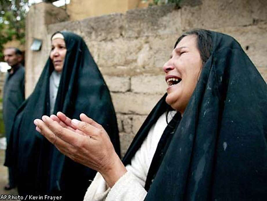 Shia arab Sadi Qader Muhamad, right, weeps as she stands in front of her home that was seized by Kurds in recent days in Kirkuk, Iraq Wednesday, April 16, 2003. (AP Photo/Kevin Frayer) Photo: KEVIN FRAYER