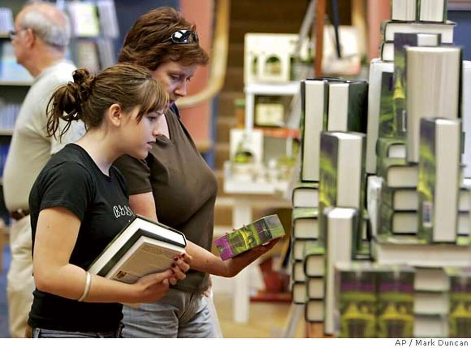 """Erica MacDonald, left, and her mother, Cathy, look over the CD version after selecting a copy of """"Harry Potter and the Half Blood-Prince"""" at Joseph Beth Booksellers in Lyndhurst, Ohio Monday, July 18, 2005. The new """"Harry Potter and the Half-Blood Prince"""" sold an astonishing 6.9 million copies in the United States in its first 24 hours _ averaging better than 250,000 sales per hour and smashing the record held by the previous Potter release. (AP Photo/Mark Duncan) Photo: MARK DUNCAN"""