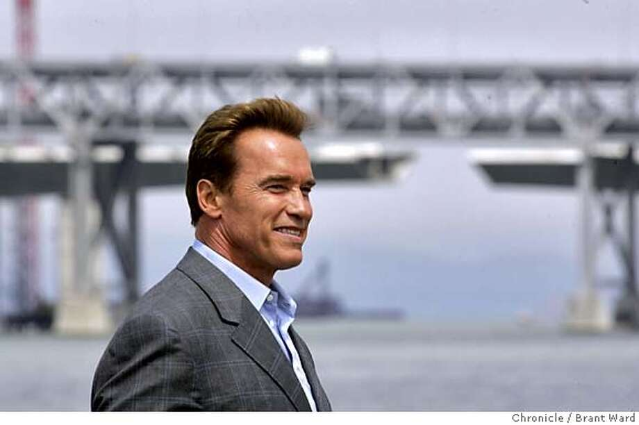 bridge282_ward.jpg  With the eastern section of the Bay Bridge in background, the Governor walked back to his limo after signing the construction bill.  Governor Arnold Schwarzenegger signed AB144 Monday to finance the construction of the new San Francisco-Oakland Bay Bridge. He was joined by Senator Don Perata and Secty of Business and Transportation Sunne McPeak as well as other state officials at the signing held at the Port of Oakland.  Brant Ward 7/19/05 Photo: Brant Ward
