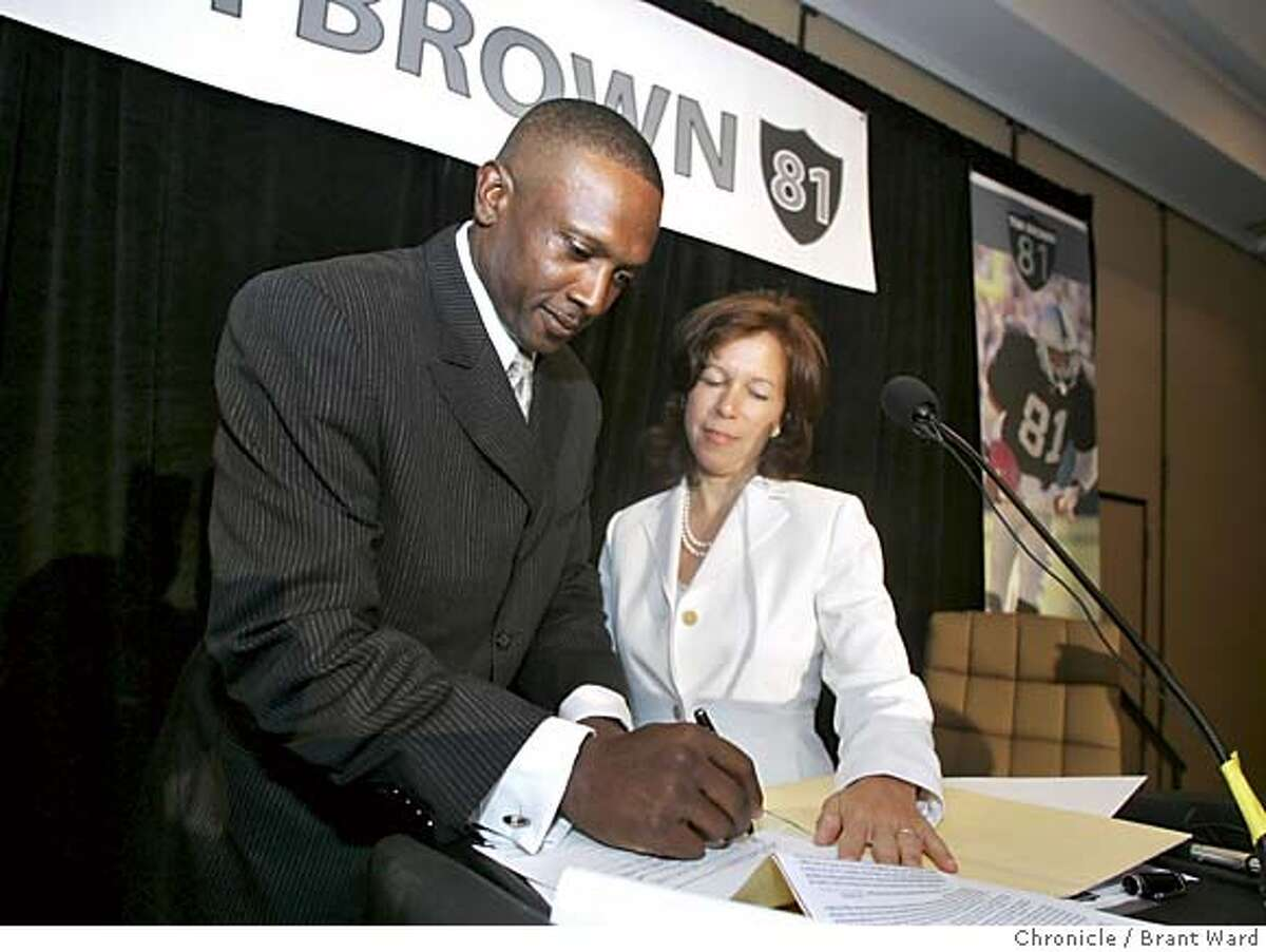 timbrown271_ward.jpg Tim Brown signs his one-day contract as Raiders Chief Executive Amy Trasco (chk spelling) watches. Tim Brown signed a one-day contract with the Oakland Raiders Monday and retired as a member of the Silver and Black. Event was held in the Grand Ballroom of the Hilton Hotel. Brant Ward 7/19/05