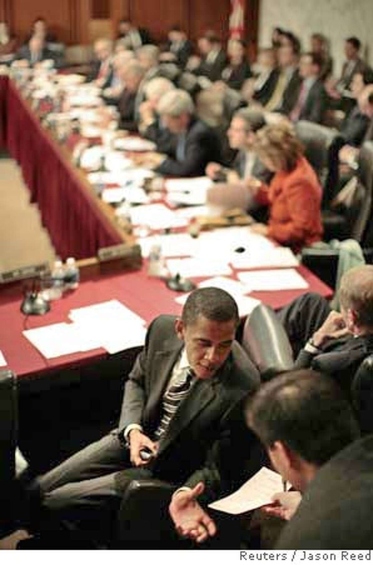 """U.S. Democratic party Senator Barack Obama (D-IL) receives a note from an aide during the Senate Foreign Relations Committee business meeting on Iraq resolution, on Capitol Hill in Washington, January 24, 2007. Democrats took the first step toward a wartime repudiation of President Bush on Wednesday, convening a Senate committee to endorse legislation declaring that the deployment of additional troops to Iraq is """"not in the national interest."""" REUTERS/Jason Reed (UNITED STATES) Ran on: 01-25-2007 Sens. Chuck Hagel, R-Neb., (left) and Richard Lugar, R-Ind., participate in the Foreign Relations Committee debate."""