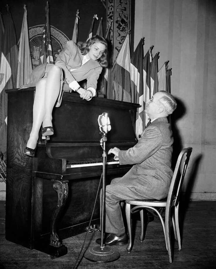 Vice President Harry S. Truman plays the piano as new movie star Lauren Bacall lies on top of it during her appearance at the National Press Club canteen in Washington in 1945. / AP1945