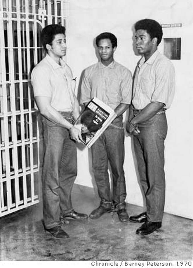 JACKSON1-B-10SEP70-MG-BP - Left to right: George Jackson, Fleeta Drumgo, and John Clutchette. For some reason Jackson is holding a current edition of LIFE magazine - probably that someone has given them for the sake of this set-up photo. San Francisco Chronicle by Photo: JACKSON1-B-24JUL01-MG-HO