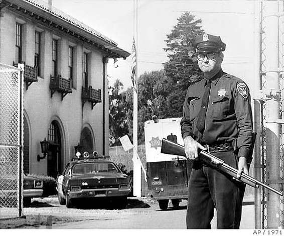 San Francisco, Aug 30, 1971--ON GUARD AT THE INGLESIDE STATION--Officer George Benner stands guard with a shotgun at the gate leading to San Francisco's Ingleside Station, left background, where the flag flies at half staff for slain Sergeant John Victor Young. He was killed at the station when a gunman burst into the station and opened fire with a shotgun. A woman clerk was also wounded during the shooting. Photo: AP