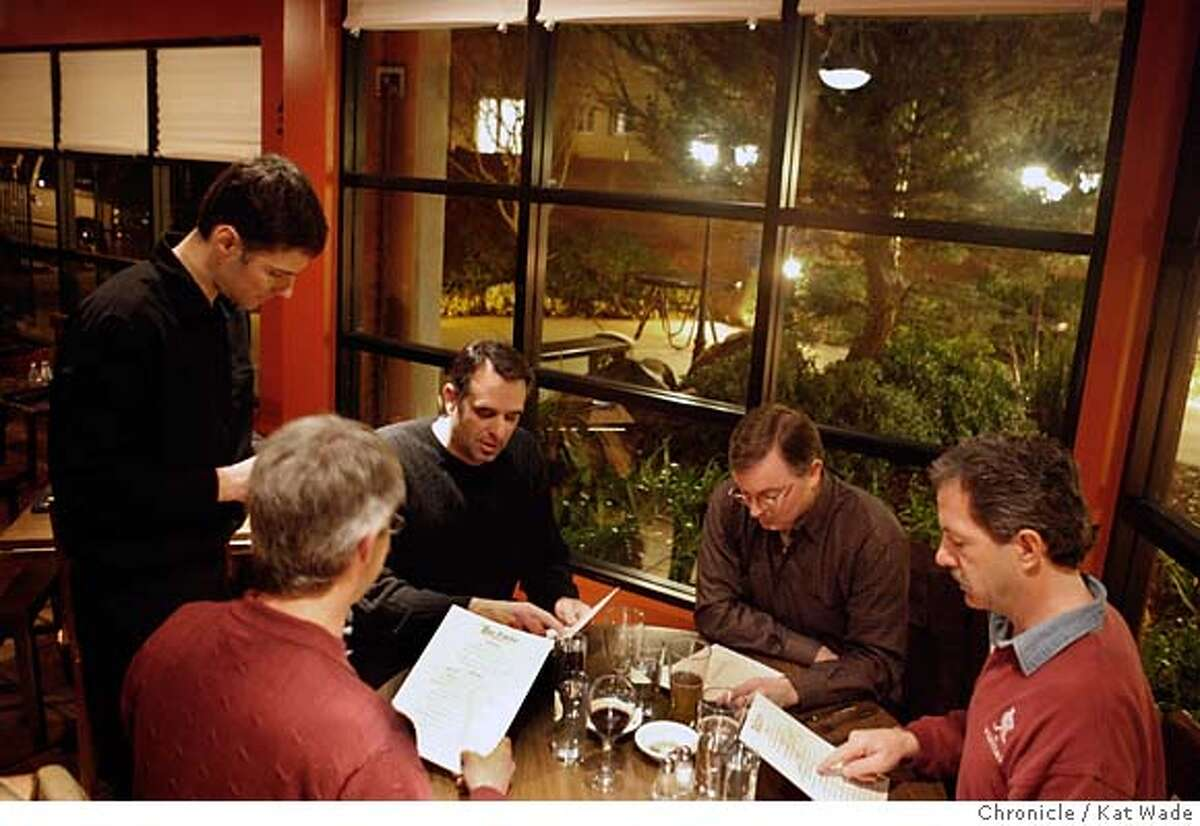 DINE24_patio_0004_KW_.jpg (L to R) Co-owner and server, Christian Momberg takes the order from members of the Lafayette Men's Book Club , Michael Inserra (CQ), Ross Goodheart, David Waal (CQ) and Kevin Foster, as they prepare to dine on a variety of South American tapas on Wednesday January 17, 2007 at The Patio a new restaurant in Lafayette that serves South American tapas . Kat Wade/The Chronicle Mandatory Credit for San Francisco Chronicle and photographer, Kat Wade, Mags out