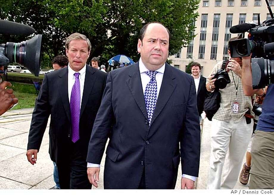 Time Magazine reporter Mathew Cooper, center, leaves U. S. District Court in Washington, Wednesday, July 6, 2005, after agreeing to cooperate with federal prosecutor's investigation into the leak of the identity of CIA operative Valerie Plame. New York Times reporter Judith Miller was ordered to jail for refusing to divulge her source. (AP Photo/Dennis Cook) Photo: DENNIS COOK