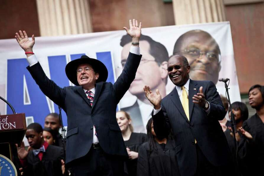 Comedian Stephen Colbert (L) holds a rally with former Republican presidential candidate Herman Cain