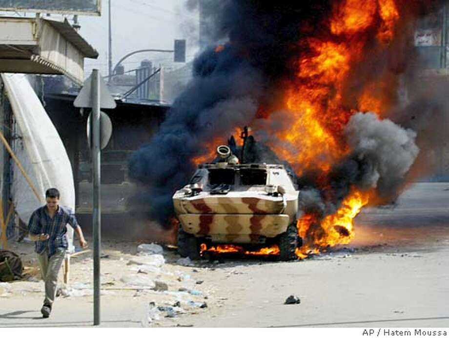 A man runs past a Palestinian security force armored carrier as it burns in the street after it was set on fire during clashes between police and militants from Hamas in Gaza City's Zeitoun neighborhood, Friday July 15, 2005. Palestinian police and Hamas militants exchanged fire in a crowded Gaza City neighborhood on Friday, and at least two people were killed and 25 wounded in some of the worst fighting among Palestinians in recent years. (AP Photo/Hatem Moussa) Photo: HATEM MOUSSA