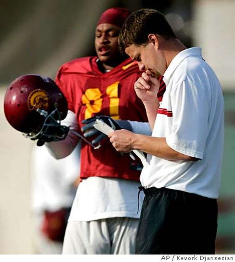 ** FILE ** Southern California football offensive coordinator Lane Kiffin, right, looks at his play list as tailback LenDale White puts on his helmet in during team practice in Los Angeles in this Friday, Dec. 30, 2005, file photo.The Oakland Raiders hired Kiffin, 31, as their coach Monday night, Jan. 22, 2007, making him the NFL's youngest head coach. (AP Photo/Kevork Djansezian) DEC. 30, 2005 FILE PHOTO EFE OUT Photo: KEVORK DJANSEZIAN