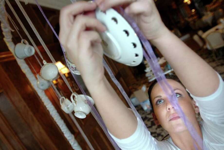Tamara Menges hangs tea cups and saucers for a tea party themed reception at the Neches Room on Crockett Street in Beaumont, Friday, January 20, 2012. Tammy McKinley/The Enterprise Photo: TAMMY MCKINLEY
