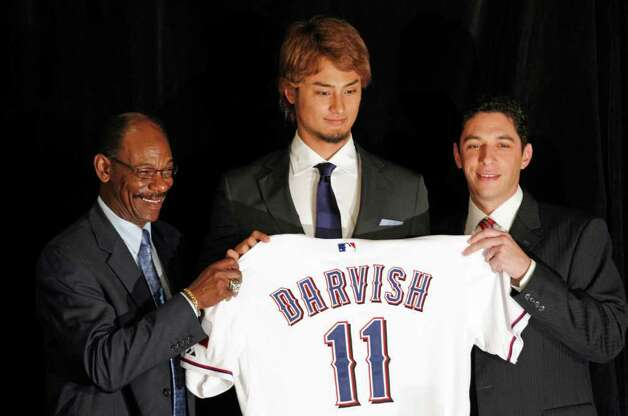 New Texas Rangers pitcher Yu Darvish (center) poses with manger Ron Washington (left) and general manager Jon Daniels on Friday in Arlington. Photo: AP