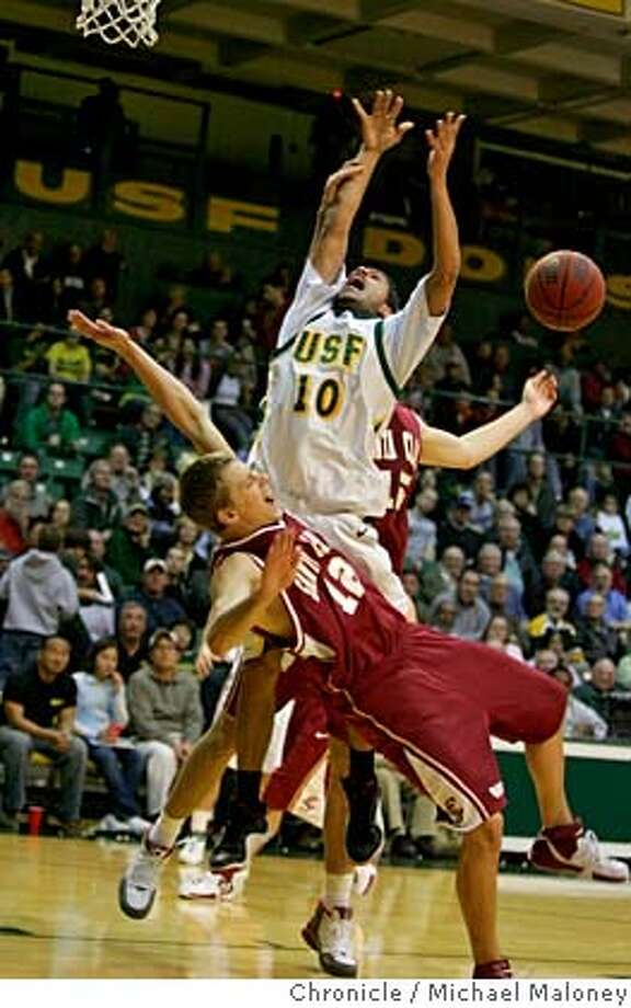 USF Dons' Manny Quezada (10) was called for an offensive foul on this play against Santa Clara's Scott Dougherty (12) in the 1st period.  University of San Francisco Dons men's basketball vs Santa Clara University Broncos at USF's Memorial Gym on Monday,  January 22, 2007.  Photo taken on 1/22/07 by Michael Maloney / San Francisco Chronicle Photo: Michael Maloney