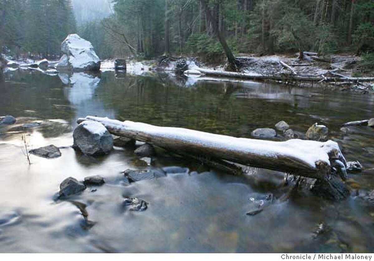 2007 FILE - Water flows under a snow topped log in the Merced River. In the winter, the Merced River flowing through the valley floor of Yosemite is at very low flows - in a normal year. Such was not the case in 1007.