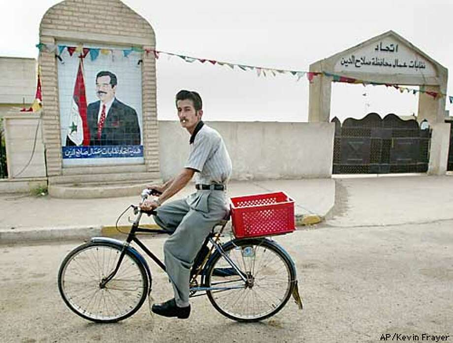 A man rides his bicycle past a mural of Iraqi President Saddam Hussein in Tikrit, Iraq Sunday April 13, 2003. Tikrit is the hometown of Saddam. (AP PHOTO/Kevin Frayer) Photo: KEVIN FRAYER