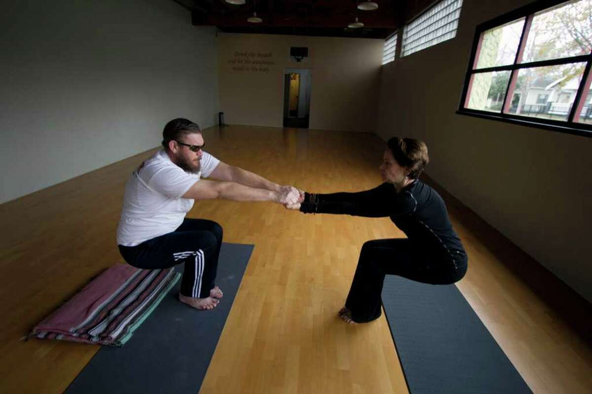 Weldon Holder and yoga instructor Pam Johnson go through an exercise at the Heights School of Yoga. Relaxation techniques help treat post-traumatic stress disorder, and the military is encouraging such activity.