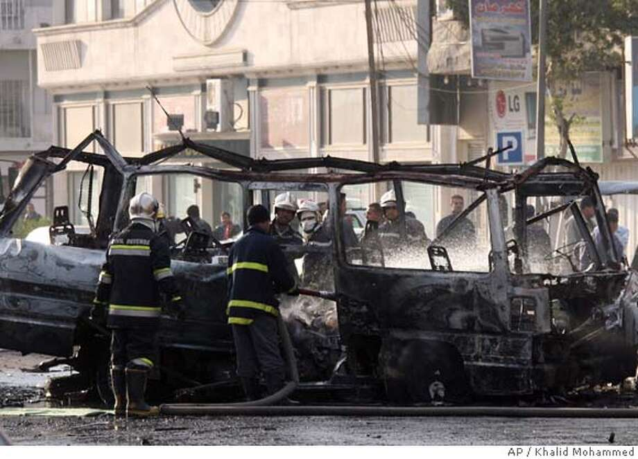 Iraqi fire fighters hose a mini bus after it blew up in central Baghdad, Iraq, Sunday Jan. 21, 2007. A bomb struck a small bus headed to a predominantly Shiite area in Baghdad on Sunday, killing six passengers and wounding 10, police said. (AP Photo/Khalid Mohammed ) Photo: KHALID MOHAMMED