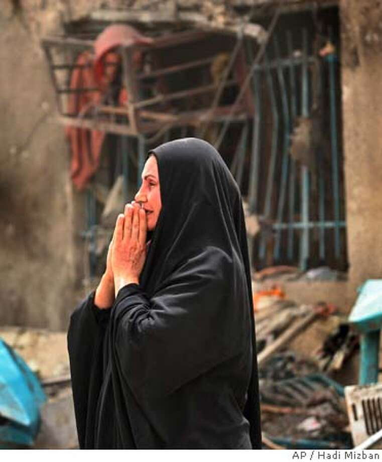 ** RETRANSMISSION TO ADD INFORMATION ** An Iraqi woman grieves as she looks at her neighbors damaged house at the scene of a suicide car bomb attack in Baghdad, Iraq Wednesday, July 13, 2005. A suicide car bomber sped to American soldiers as they distributed candy to children and detonated his vehicle Wednesday, killing up to 27 other people, U.S. and Iraqi officials said. One U.S. soldier and about a dozen children were among the dead. (AP Photo/Hadi Mizban) RETRANSMISSION TO ADD INFORMATION Photo: HADI MIZBAN