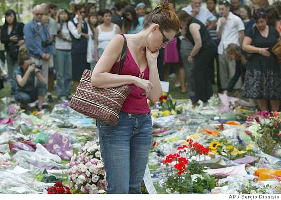 A woman reads though the flower tributes as hundreds of locals and visitors mourn the 53 confirmed dead during an Act of Remembrance ceremony at Russell Square Gardens, in London, Friday, July 15, 2005. As the death toll rises to 53, police continue forensic searches in west Yorkshire as they hunt the masterminds behind last Thursday's 7/7 terrorist attacks in London. (AP Photo/Sergio Dionisio) Photo: SERGIO DIONISIO