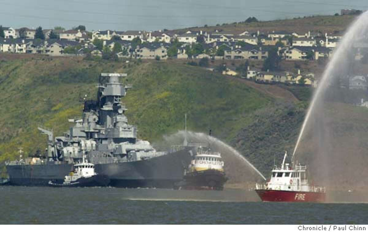 IOWA22A-C-21APR01-SZ-PC The battleship USS Iowa was towed through the Carquinez Strait by a floatilla of tugboats and was accompanied by a fireboat spraying streams of water on its way to the mothball fleet Saturday. PAUL CHINN/S.F. CHRONICLE CAT