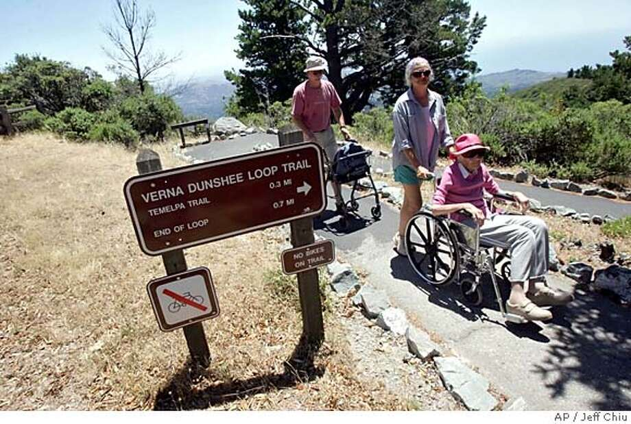 Florence Ahlers, 91, of Corte Madera, Calif., is pushed in a wheelchair by daughter-in-law, Sandra Ahlers, as her son, Kim, follows with her walker along Verna Dunshee Loop Trail on Mount Tamalpais in Mill Valley, Calif., Tuesday, July 12, 2005. California will repair and remodel its 270 parks to settle a class action lawsuit charging the nation's largest state park system has inadequate access and services for disabled visitors. The changes, to be implemented during the next 11 years, could cost thestate more than $100 million, officials said Tuesday in announcing the settlement. (AP Photo/Jeff Chiu) Photo: JEFF CHIU