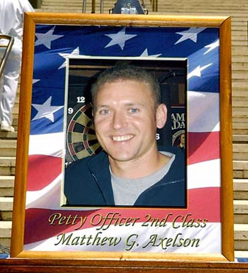 >>GY AP10/7.11.05/GREGORY YAMAMOTO PHOTO  Photo of Petty Officer 2nd Class Mathew G Axelson displayed at the Memorial Service at the National Memorial Cemetery of the Pacific for Lt Michael P Murphy, ITCS (SEAL) Daniel R Healy, STG2 (SEAL) Matthew G Axelson, MM2(SEAL) Shane E Patton, QM2(SEAL) James E Suh