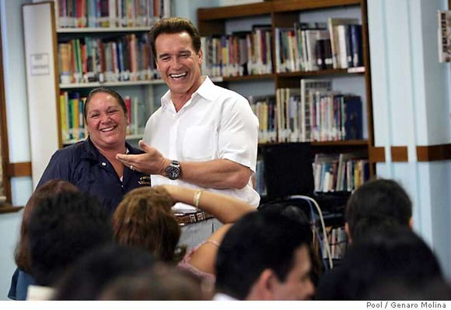 POOL PHOTO. California Governor Arnold Schwarzenegger spends a light moment with parent Elva Navarro after he met with students, parents, faculty and members of the media at Thomas Edison Junior High School Wednesday morning. Gov. Schwarzenegger was at the school to discuss the state budget for education. Navarro is a parent volunteer at the school. POOL PHOTO by Genaro Molina/Los Angeles Times Photo: Genaro Molina