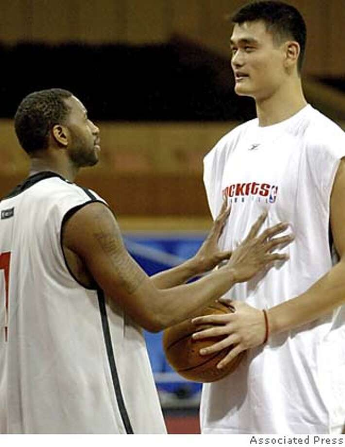 Houton Rockets guard Tracy McGrady, left, tries to get Houton Rockets center Yao Ming, right, to relax during a training session in Shanghai, China Wednesday Oct 13, 2004. The first-ever NBA preseason game in China between Houston Rockets and the Sacramento Kings is to held on Thursday in Shanghai. (AP Photo/str) ** ONLINE OUT, CHINA OUT ** Ran on: 11-02-2004  Tracy McGrady, acquired from the Magic, joins Yao Ming to give the Rockets what could be the league's top one-two punch. ONLINE OUT, CHINA OUT