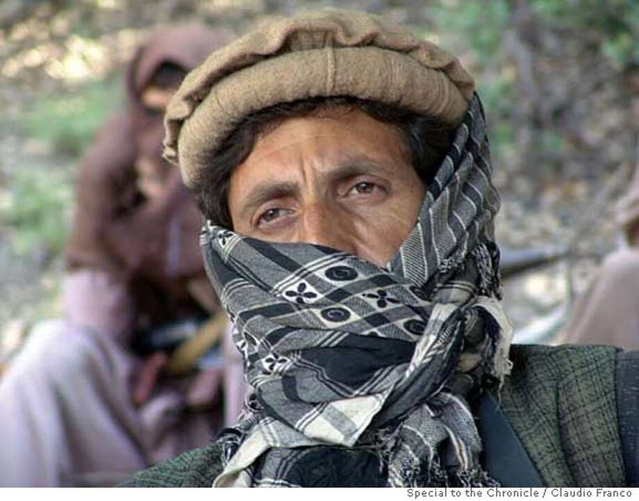 Afghan_rebels 2: Commander Musa Khan at the interim base, Kunar Province Afghanistan (the precise location - in terms of district - is unclear; I believe we were in Pech District - even if we took off from Chowki/Chawkay - bot honoestly I am not 100% sure). Musa Khan was in his later thirties, and was a veteran of the anti-Soviet Jihad. He had been ordered to attend to the meeting by his Commander and was often in touch with the leadership during the hours spent together. He had to make sure with the leaders before allowing a camera to function but they all looked somehow keen about being photographed once the way had been cleared via radio.Photo Credit: Claudio FrancoSpecial to the Chronicle, 2006 All images: Chowky/Pech Districts, Kunar Province, Afghanistan 10/2006 Photo: Claudio Franco