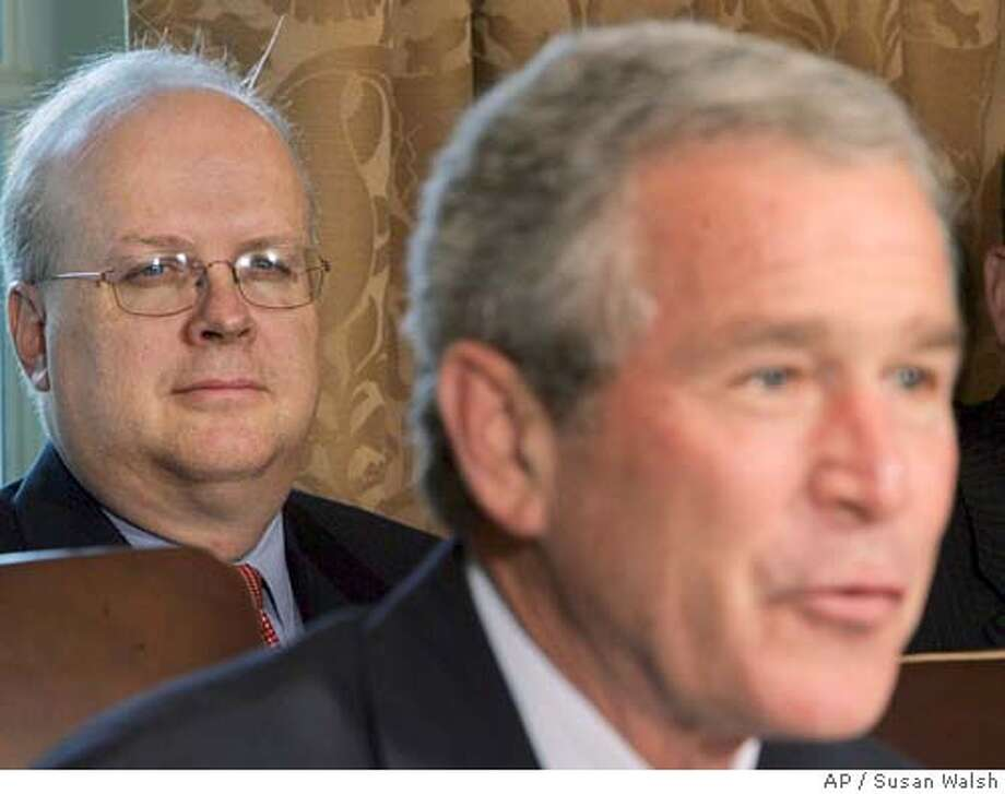 Deputy Chief of Staff Karl Rove, left, listens as President Bush comments during a meeting in the Cabinet Room of the White House, Wednesday, July 13, 2005. Bush said Wednesday that he will not comment on top political adviser Karl Rove's role in leaking the identity of a CIA operative while the investigation is ongoing. (AP Photo/Susan Walsh) Photo: SUSAN WALSH