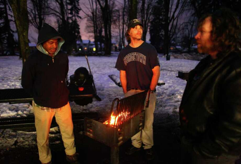 From left, Douglas Schmidt, Shayne Lewis and Lonnie Johnson gather around a fire outside the Auburn warming Shelter at Veterans Memorial Park on Friday, January 20, 2012. The trio were burning wood from downed trees in the park. The shelter, organized by the City of Auburn and the Auburn Food Bank, provided a place for homeless and people without electricity.  An ice storm wreaked havoc in the area, bringing down trees and power lines. Power was out in large parts of the area. Photo: JOSHUA TRUJILLO / SEATTLEPI.COM