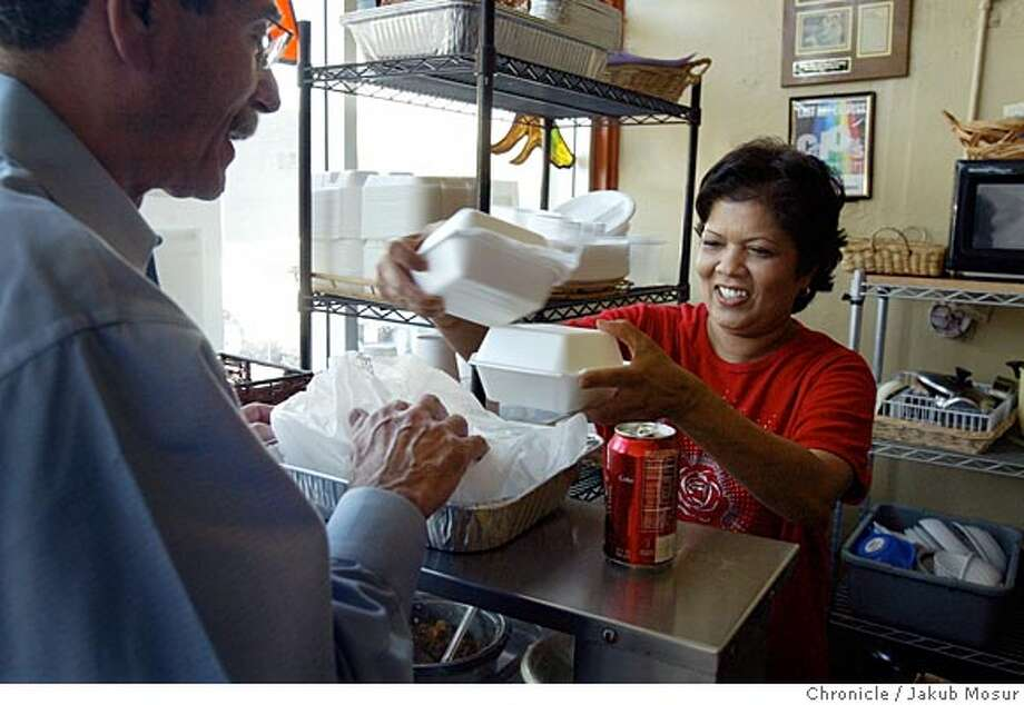 Customer David Bernstein, who came from Oakland for a meal, picks up his to go order from Saras Rao at her Indo-Fijian restaurant, called Curry Corner, in Hayward. Event on 7/6/05 in Hayward. JAKUB MOSUR / The Chronicle Photo: JAKUB MOSUR