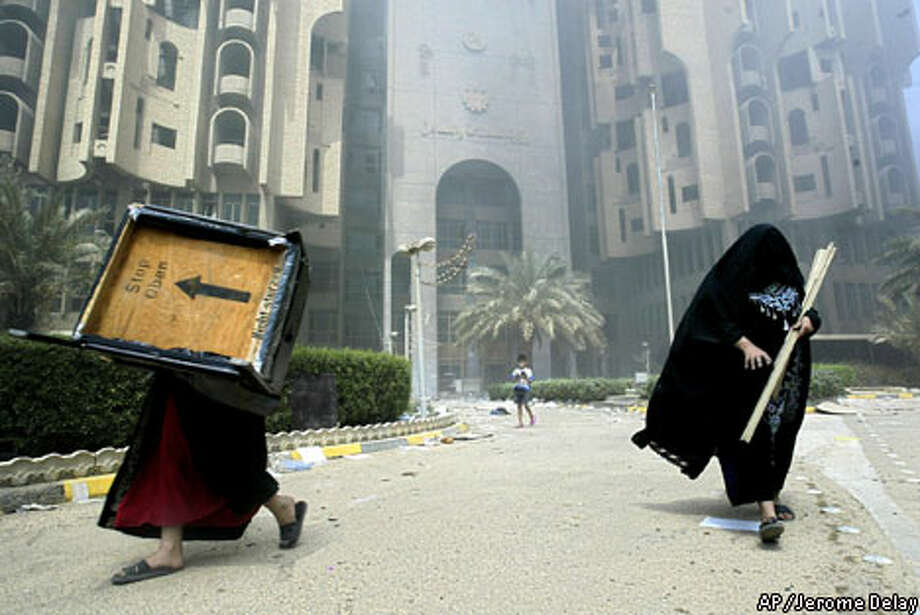 Two Iraqi women carry furniture away from a burning government building in downtown Baghdad. Associated Press photo by Jerome Delay