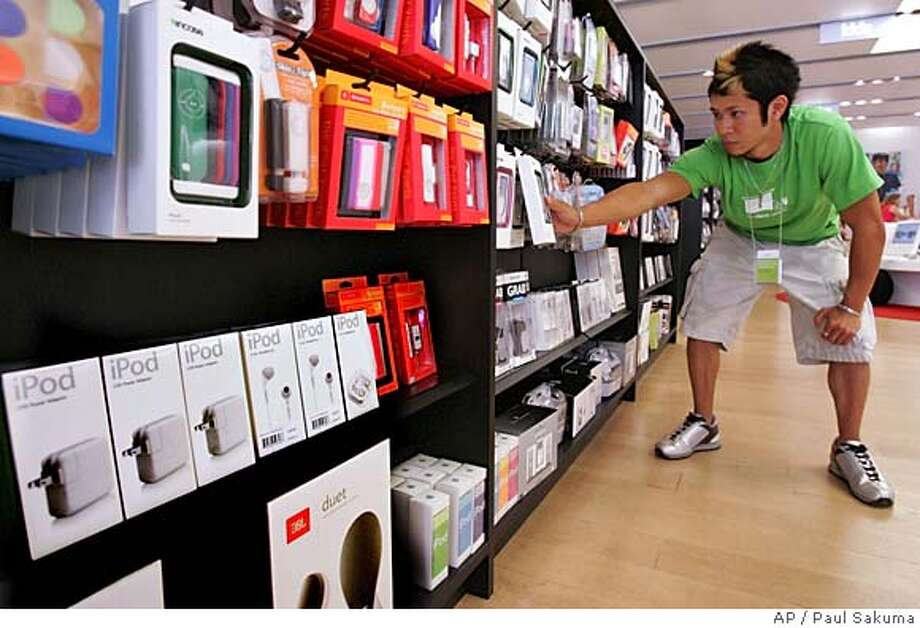 Apple Computers Inc. store salesman Brian Tong straightens up packages of various accessories for the very popular Apple iPod at the Apple store in Palo Alto, Calif., Tuesday, July 12, 2005. Apple Computer Inc. is expected to report third-quarter earnings Wednesday, July 13,2005, after the stock market's close.(AP Photo/Paul Sakuma) Photo: PAUL SAKUMA