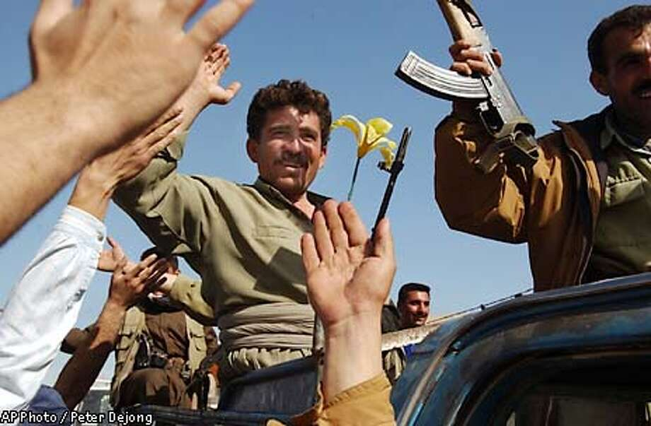 Residents cheer the arrival of Kurdish forces in the center of Kirkuk, northern Iraq, Thursday April 10, 2003. Aided by American special forces in their advance Kurdish troops took over Kirkuk Tursday, facing little resistance. (AP Photo/Peter Dejong) Photo: PETER DEJONG