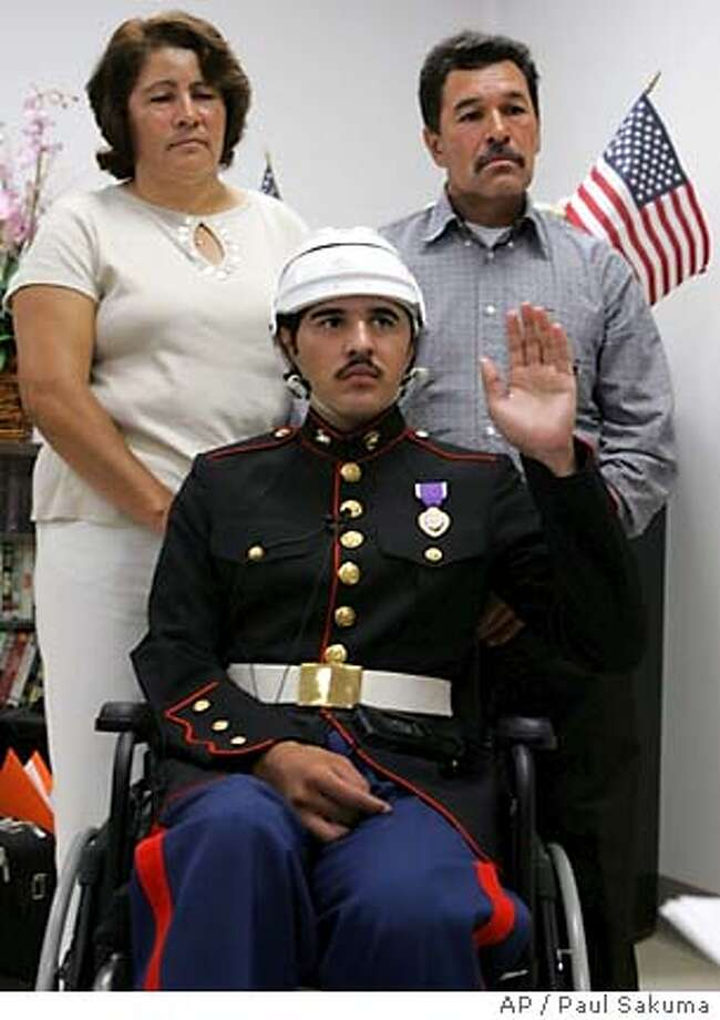 Marine Lance Cpl. Angel Gomez holds up his left arm during a ceremony at the Veterans Hospital in Palo Alto, Calif., Thursday, July 14, 2005 as his parents Paulino and Antonia Gomez stands behind. The U.S. Citizenship and Immigration Services gave Gomez his U.S. citizenship after he was injured in an explosion outside of Bagdad, Iraq in April. Gomez sustained head wounds and was unable to hold up his right arm during the ceremony. (AP Photo/Paul Sakuma) Photo: PAUL SAKUMA