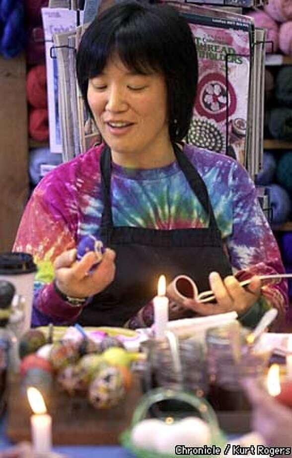 Lake Hanyu compares her egg with a photo in a book.  Ukrainian egg painting class at Rainbow Fabrics in Fairfax .Photo By Kurt Rogers Photo: Kurt Rogers