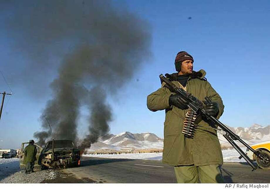 An Afghan police officer stands guard near a burning vehicle which was carrying foreigners after a suicide bomb attack in Logar province, some 40 kilometers (25 miles) south of Kabul, Afghanistan, Friday, Jan. 12, 2007. A suicide bomber rammed his explosives-filled car into a two-vehicle convoy carrying foreigners south of the Afghan capital on Friday, a police official said. (AP Photo/ Rafiq Maqbool) Photo: RAFIQ MAQBOOL