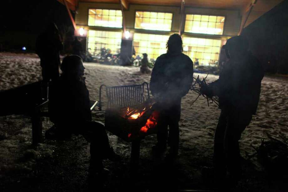 People gather around a fire outside the Auburn warming Shelter at Veterans Memorial Park on Friday, January 20, 2012. The group burned wood from downed trees in the park. The shelter, organized by the City of Auburn and the Auburn Food Bank, provided a place for homeless and people without electricity.  An ice storm wreaked havoc in the area, bringing down trees and power lines. Power was out in large parts of the area. Photo: JOSHUA TRUJILLO / SEATTLEPI.COM