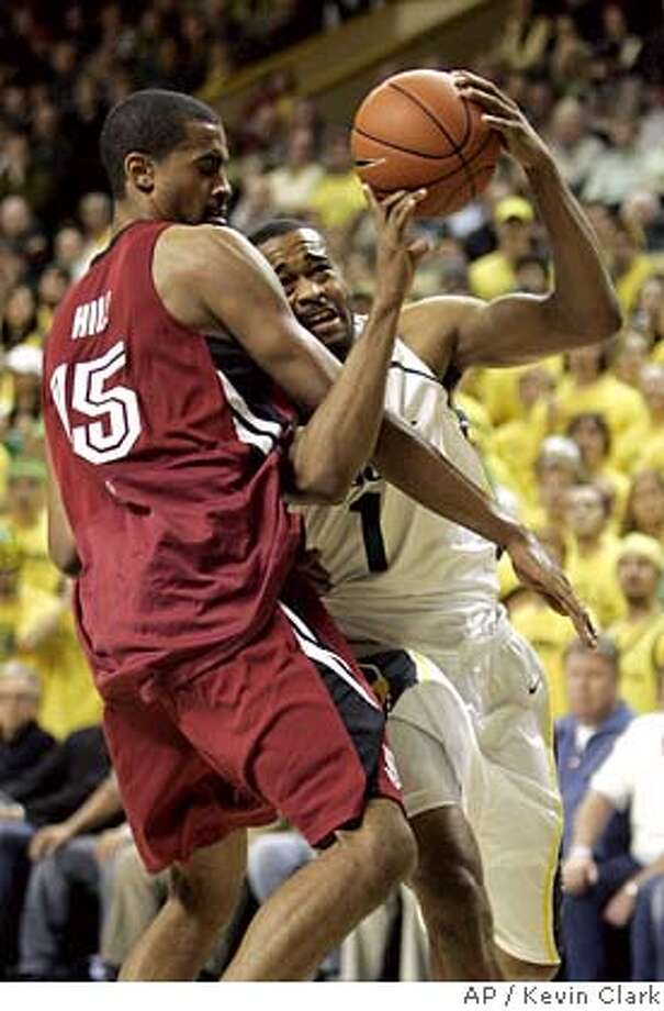 Oregon's Malik Hairston, right, is fouled on a drive to the basket by Stanford's Lawrence Hill in first-half action of their basketball game in Eugene, Ore. Thursday, Jan. 18, 2007. (AP Photo/Kevin Clark) Photo: KEVIN CLARK