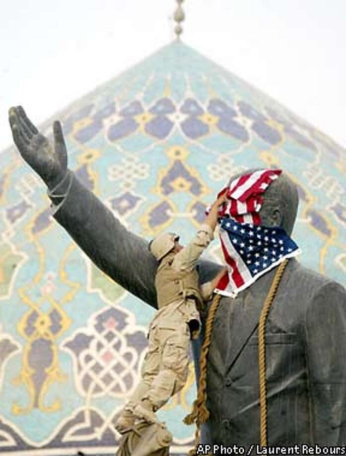 Cpl Edward Chin from New York of the 3rd battalion, 4th Marines regiment, set up the star and stripes flag on the face of Iraqi President Saddam Hussein's statue before to tear down it, in downtown Bagdad, Wednesday, April 9, 2003. (AP Photo/Laurent Rebours) Photo: LAURENT REBOURS