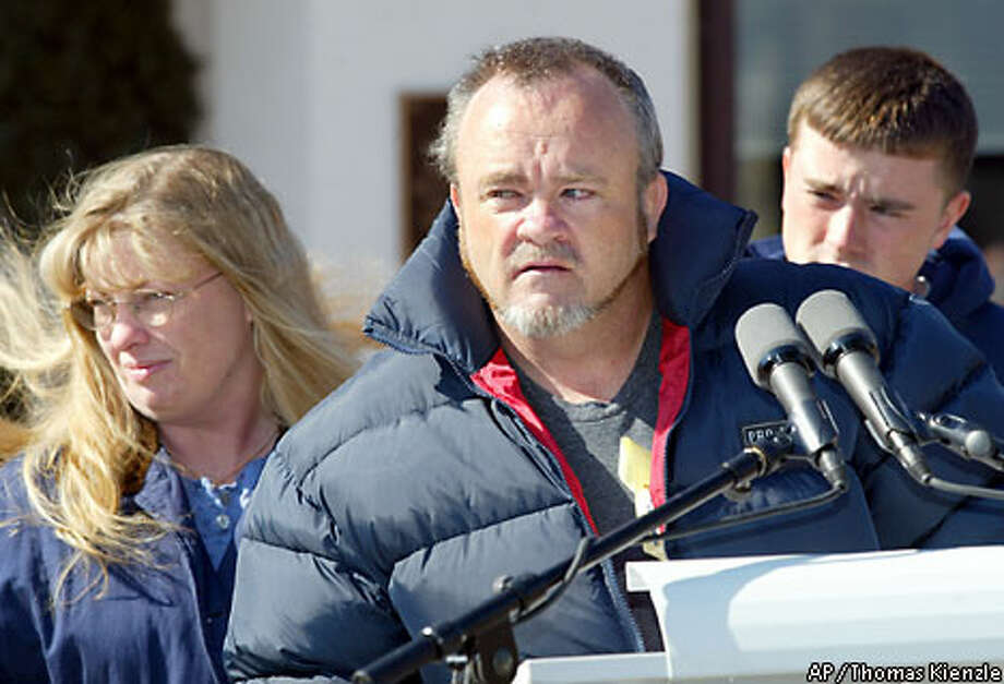 Gregory Lynch (center), father of rescued U.S. POW Pfc. Jessica Lynch, appears with his wife, Deadra, at the Landstuhl, Germany, medical center where their daughter was being treated. The parents have told reporters that they are not ready to contemplate the sale of the rights to their daughter's story. Associated Press photo by Thomas Kienzle