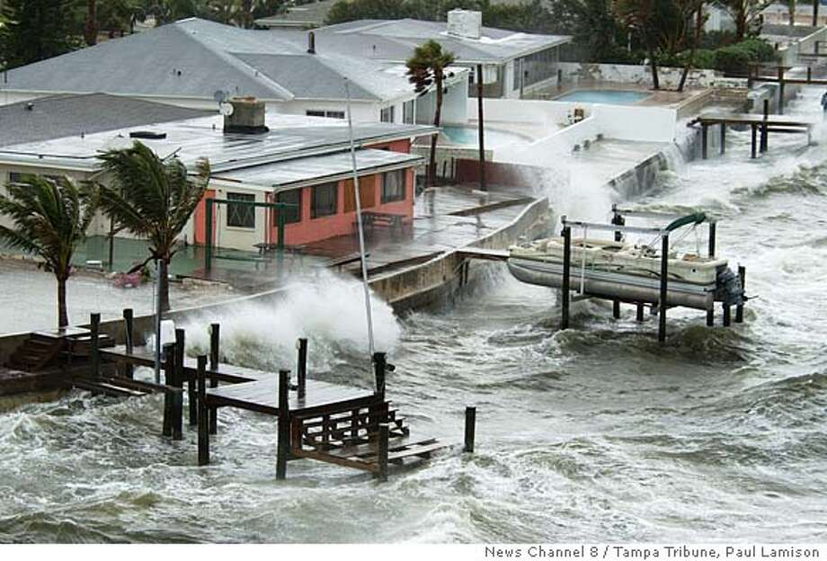 Waves crash against a seawall at Tropical Point a residential area of Tampa Bay, in St. Petersburg, Fla., Saturday, July 9, 2005. Hurricane Dennis dealt a glancing blow to the Florida Keys on Saturday, knocking out power and leaving streets flooded with seaweed as it roared toward the storm-weary Gulf Coast, where nearly 1.4 million people were under evacuation orders. (AP Photo/News Channel 8/Tampa Tribune, Paul Lamison) Photo: PAUL LAMISON