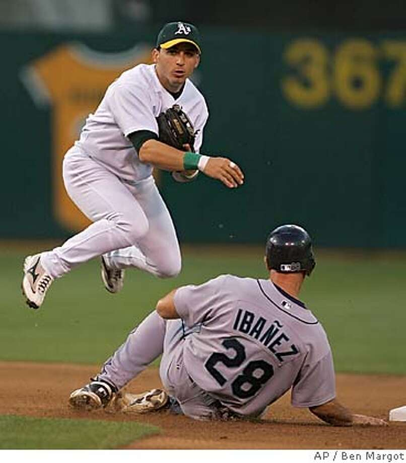 Oakland Athletics' Marco Scutaro hops over Seattle Mariners' Raul Ibanez (28) after completing a double play in the fourth inning Wednesday, June 29, 2005, in Oakland, Calif. Seattle's Bret Boone was out at first base. (AP Photo/Ben Margot) Photo: BEN MARGOT