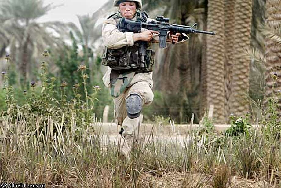 Spc. Daniel Yoo of Task Force 2-69 Armor, 3rd Brigade Combat Team, 3rd Infantry Division from Fort Benning, Ga., runs for a defensive position after spotting movement several hundred meters away during a search-and-destroy patrol to locate enemy troops and equipment in northern Baghdad, Iraq, Tuesday, April 8, 2003. (AP Photo, Dallas Morning News/David Leeson) Photo: DAVID LEESON